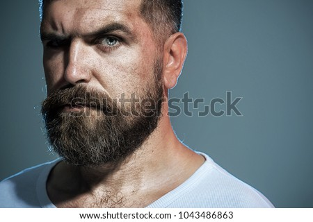 Bearded man. Portrait of masculinity. Stylish hipster brutal man with beard, mustache, beautiful hairstyle. Serious unshaven man. Sexy look of male model. Advertising barbershop concept. Copy space.