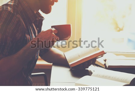 bearded man reading book with coffee or tea