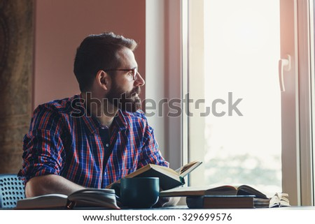 Bearded man reading books at table