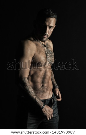 Bearded man shirtless with fit torso. Man with tattoo design on skin. Fashion model buckle leather belt in jeans. Sportsman with six pack and ab. Fitness with sport and bodycare, vintage filter.