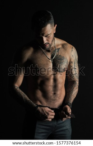 Bearded man shirtless with fit torso. Man with tattoo design on skin. Fashion model buckle leather belt in jeans. Sportsman with six pack and ab. Fitness with sport and bodycare.
