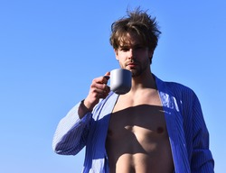Bearded man, short beard. Caucasian macho with moustache and ruffled hair in blue striped pajamas showing strong torso with six packs and holding cup on blue sunny sky background, morning concept