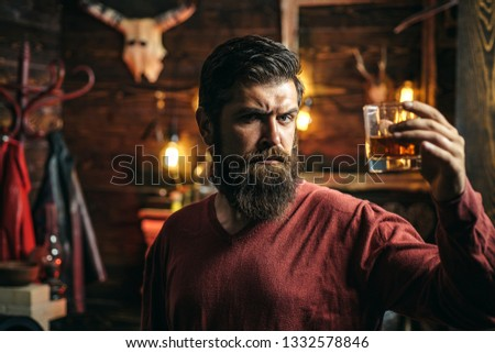 Bearded man sitting at bar. Handsome man drinking olcohol while sitting at the bar. Handsome pensive man is holding a glass of whiskey