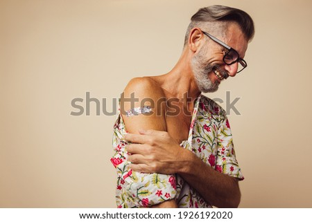 Bearded man smiling with bandage on arm after receiving immunity vaccine. Mature man looking relaxed after receiving covid-19 vaccine.