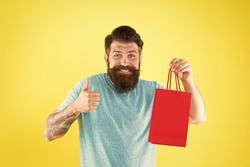 Bearded man smiling with purchase. Impulse purchase. Shopping concept. Shop store mall boutique. Buy product. Aspects can influence customer decision making behavior. Happy hipster hold paper bag.
