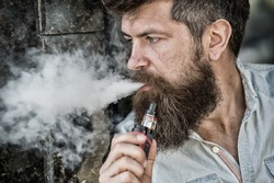 Bearded man smokes vape, white clouds of smoke. Electronic cigarette concept. Man with long beard looks relaxed. Man with beard and mustache on calm face, dark background, defocused