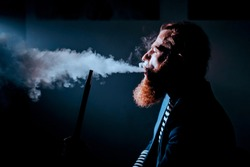 bearded man smoking a hookah in a dark room. hookah lifestyle and smoking concept. portrait of a sailor with a hookah. Toned image