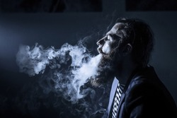 bearded man smoking a hookah in a dark room. hookah lifestyle and smoking concept. portrait of a sailor with a hookah close. Toned image