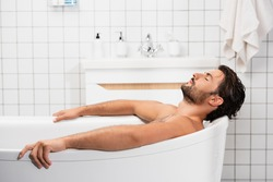 Bearded man taking bath with closed eyes at home