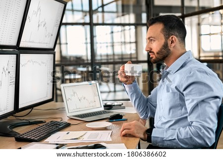 Bearded man trader sitting at desk in front of monitors at office holding cup drinking hot coffee using trading bot program make trades on user behalf cryptocurrency exchange looking at monitor with