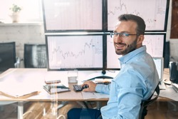 Bearded man trader wearing eyeglasses sitting at desk at office loooking at digital screens with candlestick charts stock flows monitoring bitcoin cryptocurrency changes trading concept looking back
