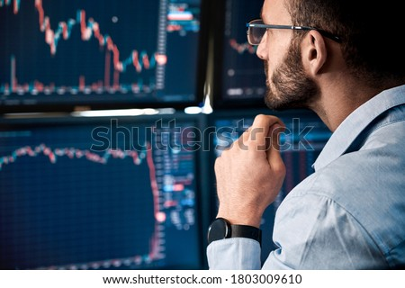 Bearded man trader wearing eyeglasses sitting at desk at office monitoring stock market looking at monitors analyzing candle bar price flow touching chin concerned trading concept close-up