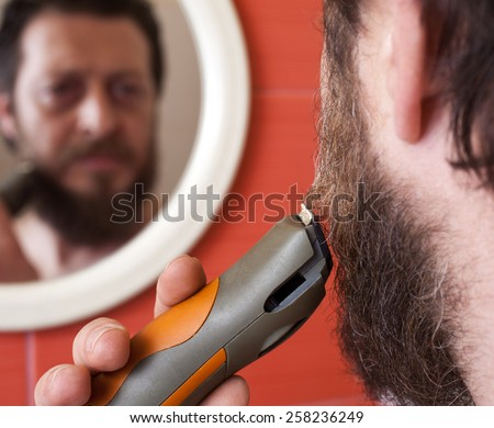 Bearded man trim his beard with electric shaver.