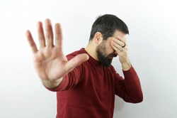 Bearded man wearing casual clothes  on white background covering eyes with hand and doing stop gesture. Embarassed and negative concept