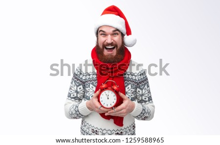 Bearded man wearing red santa hat and warm winter pullover holding clock five to twelfe and waiting for christmas countdown isolated on white background #1259588965