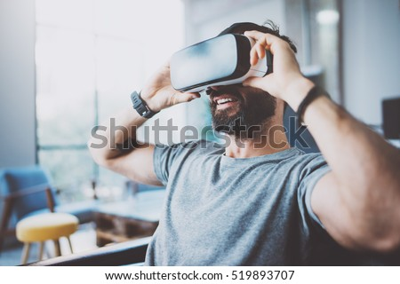 Bearded man wearing virtual reality goggles in modern coworking studio. Smartphone using with VR headset. Horizontal, blurred #519893707