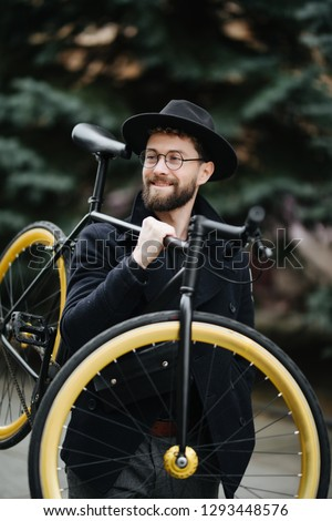 Bearded man with a fixie bicycle. Low angle view of confident young bearded man carrying his bicycle on shoulder and looking at camera while walking outdoors. stylish businessman with a bike.