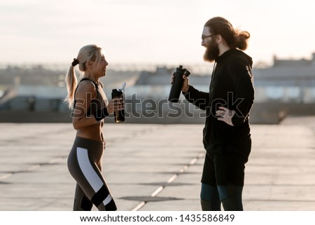Bearded man with a girl drinking water from a sports bottle resting from Jogging outdoors. Morning jog on the waterfront. Family leads a healthy lifestyle