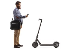 Bearded man with a laptop case renting a scooter with a mobile phone isolated on white background