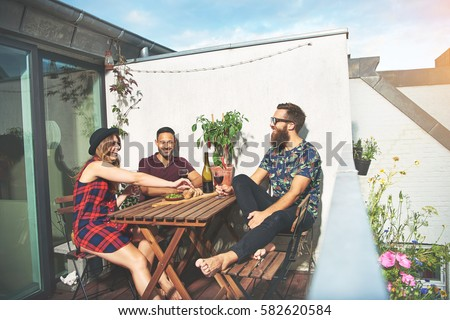 Bearded man with attractive young couple drinking wine at wooden table on roof in European city Foto stock ©