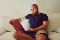 Bearded Man with blue light blocking eye glasses (yellow amber lens) working with laptop sitting on sofa