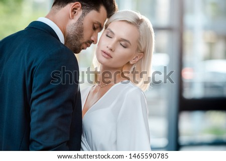 bearded man with closed eyes flirting with beautiful blonde coworker in office