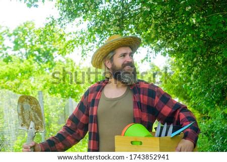 Bearded man with gardening tools. Attractive man working in garden. Professional gardener. Gardener work. Farm. Happy bearded man in garden. Plants. Garden tools. Gardening. Eco-farm. Work in garden.