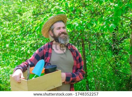 Bearded man with gardening tools. Plants. Garden tools. Gardening. Eco-farm. Work in garden. Attractive man working in garden. Professional gardener. Gardener work. Farm. Happy bearded man in garden.