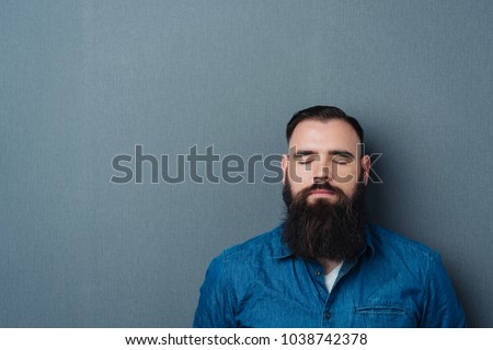 Bearded man with his eyes closed and a calm expression against a dark studio background with copy space #1038742378