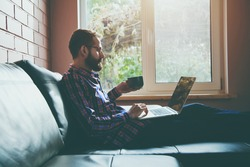 bearded man with laptop drinking coffee or tea