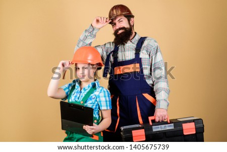Bearded man with little girl. Repairman in uniform. Engineer. construction worker. Builder or carpenter. Repair. Childrens creativity. Father and daughter in workshop. Concentrated on your problem. #1405675739