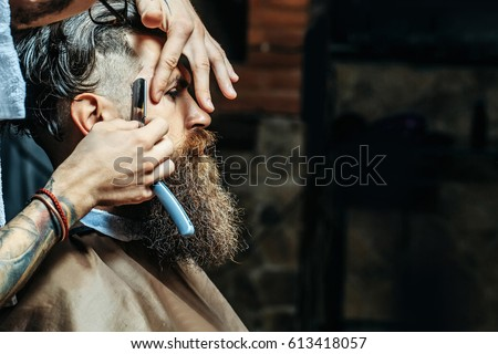 Bearded man with long beard, brutal, caucasian hipster with moustache, getting stylish hair shaving, haircut, with razor by barber or hairdresser with tattoo on hands at barbershop #613418057