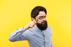 bearded man with magnifier over yellow  background, search concept