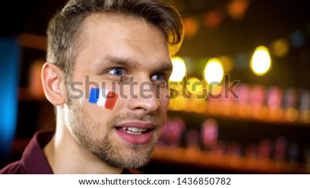 Bearded man with painted flag of france watching world tournament in bar #1436850782