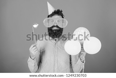 Bearded man with party accessories, surprise concept. Man with paper lips, enormous crazy glasses and balloons isolated on red background. Hipster with long beard wearing pink shirt and birthday cap. #1249230703