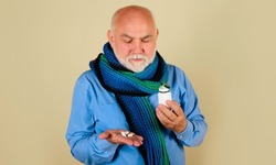 Bearded man with pills in hand. Male with bottle of medicine pill. Sick man taking tablet.