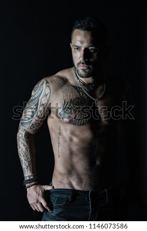 Bearded man with strong torso. Man with tattooed arm and chest. Tattoo model with sexy belly. Sportsman or athlete in fashion jeans. Bodycare or fitness and sport in vintage filter. #1146073586