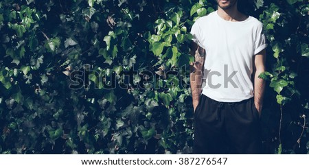Bearded man with tattoo wearing blank white tshirt and black sunglasses.Green garden wall background. Wide closeup #387276547