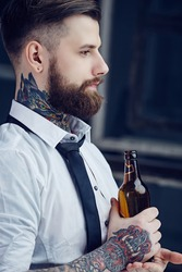 Bearded man with tattooes on his arm in a white shirt drinking beer.