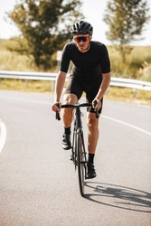 Bearded mature man in active wear and protective helmet doing sport activity on bike. Strong cyclist in mirrored glasses leading healthy lifestyle.