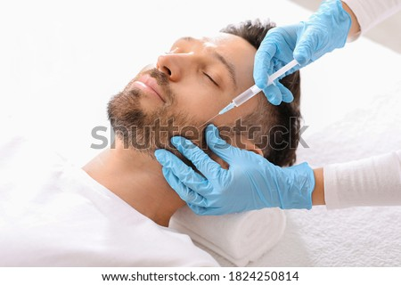 Bearded middle aged man getting beauty injection in salon. Cosmetologist hands in blue rubber gloves doing anti-aging procedure for handsome man in clinic. Face care, male cosmetology concept
