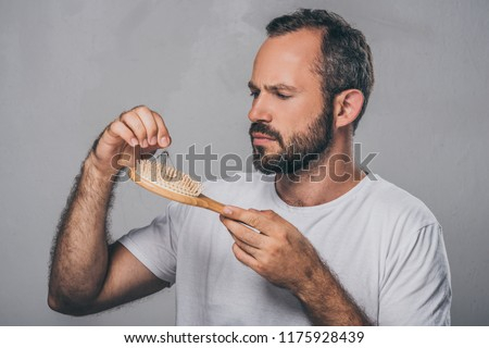 bearded middle aged man holding hairbrush, hair loss concept