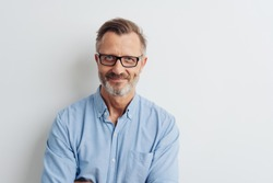Bearded middle-aged man wearing glasses posing over a white studio background with copy space looking at the camera with a friendly smile