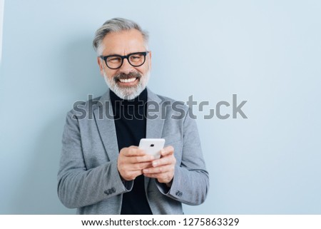 Bearded middle-aged man with grey hair, holding smartphone, looking at camera and laughing. Half-length front portrait against blue wall background with copy space