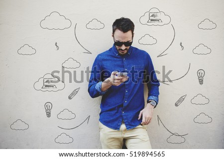 Bearded modern businessman concentrated reading world news in internet via mobile phone. Hipster guy text messaging with friend via cell telephone. Infographics pattern elements and multimedia signs #519894565
