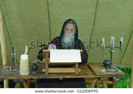 Bearded monk chronicler writes on the historic festival ancient scroll