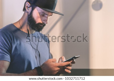 8dc5e453d6f Bearded pensive man wearing black snapback cap standing on cafe with  headphones. Men using mobile