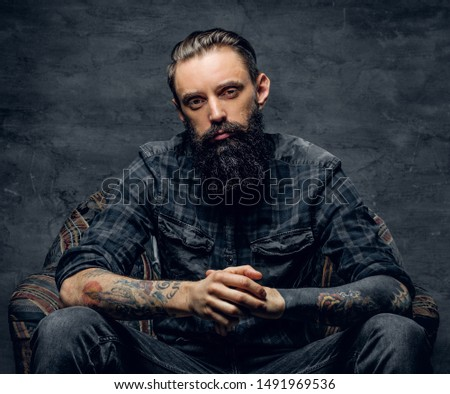 Bearded pensive man with tattooes is sitting on the armchair at dark room.