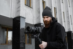 Bearded Professional videographer in black hoodie holding professional camera on 3-axis gimbal stabilizer. Filmmaker making a great video with a professional cinema camera. Cinematographer.