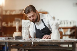 Bearded sculptor measures stone woman torso to make copy of it from limestone at creative studio.